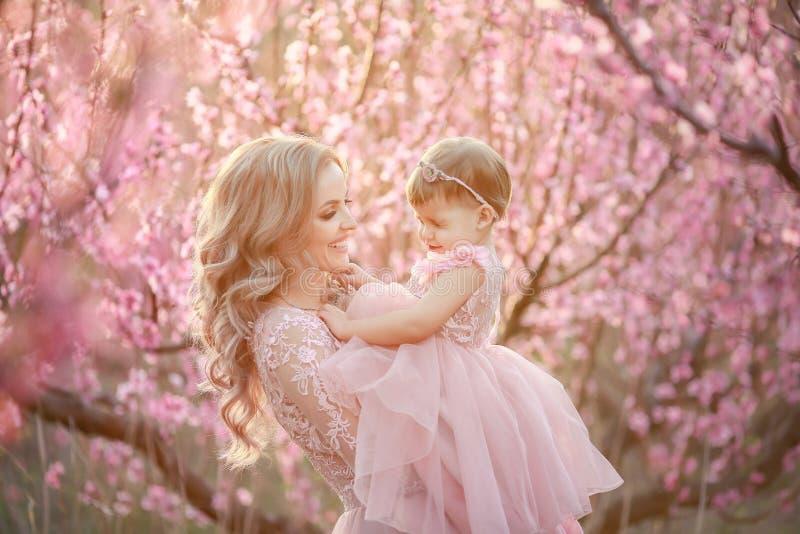 年轻美丽的母亲画象有她的女孩的 仍然关闭爱的家庭 拿着她的可爱的妇女 免版税库存照片