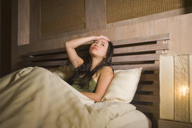 年轻美丽的沮丧和哀伤的亚裔中国妇女有说谎在床在夜失眠的遭受的忧虑重音的失眠和 免版税图库摄影