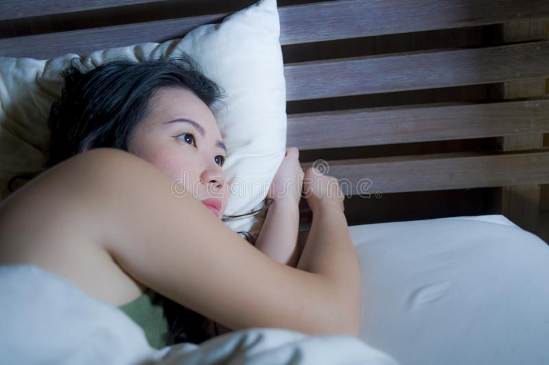 年轻美丽的沮丧和哀伤的亚裔中国妇女有说谎在床在夜失眠的遭受的忧虑重音的失眠和 库存图片