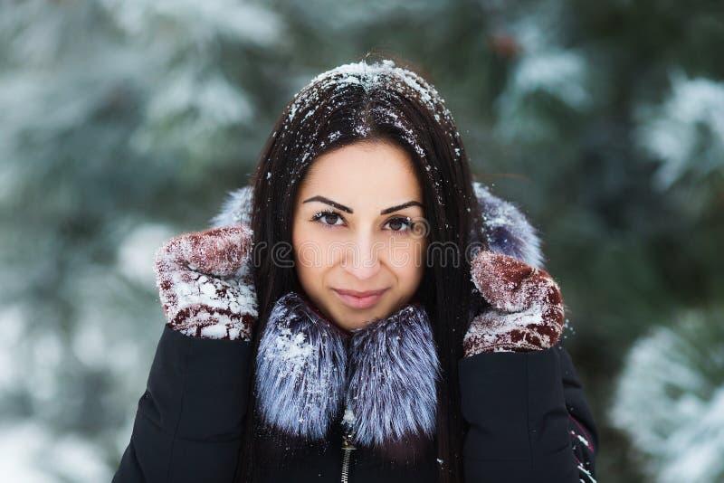 年轻美丽的深色的在雪盖的妇女佩带的手套冬天画象  降雪的冬天秀丽时尚概念 库存图片