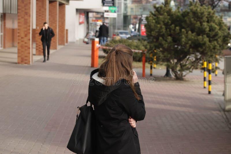 年轻美丽的深色的女孩在智能手机沟通与在城市街道上的一个人 在每天通信恋人的小配件 免版税图库摄影