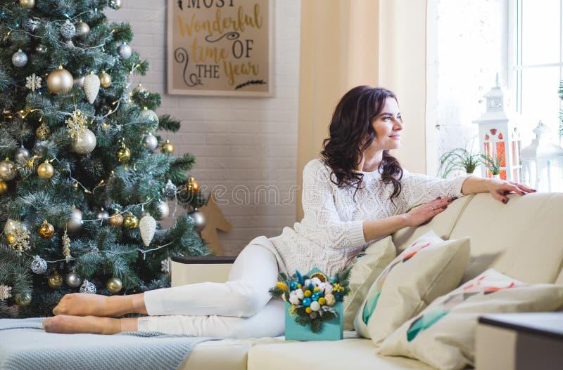 年轻美丽的深色的妇女佩带的白色被编织的毛线衣在家由窗口 库存照片
