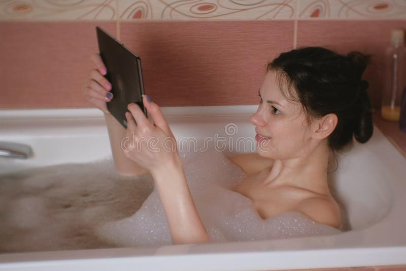 年轻美丽的深色的妇女洗浴并且观看在片剂的录影 免版税库存照片