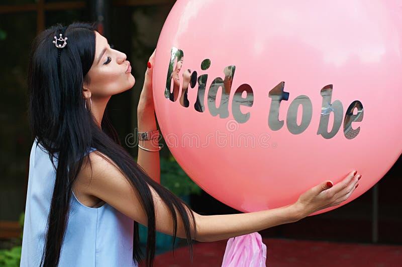 年轻美丽的深色的新娘是与黑发和银加冠对亲吻她的桃红色bachelorette党气球的此 免版税库存图片