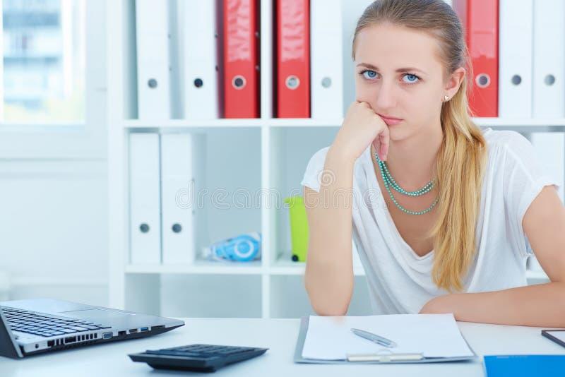 年轻美丽的疲乏的女孩在他的手在一张书桌在办公室和看上照相机坐被扶植的头 免版税库存图片
