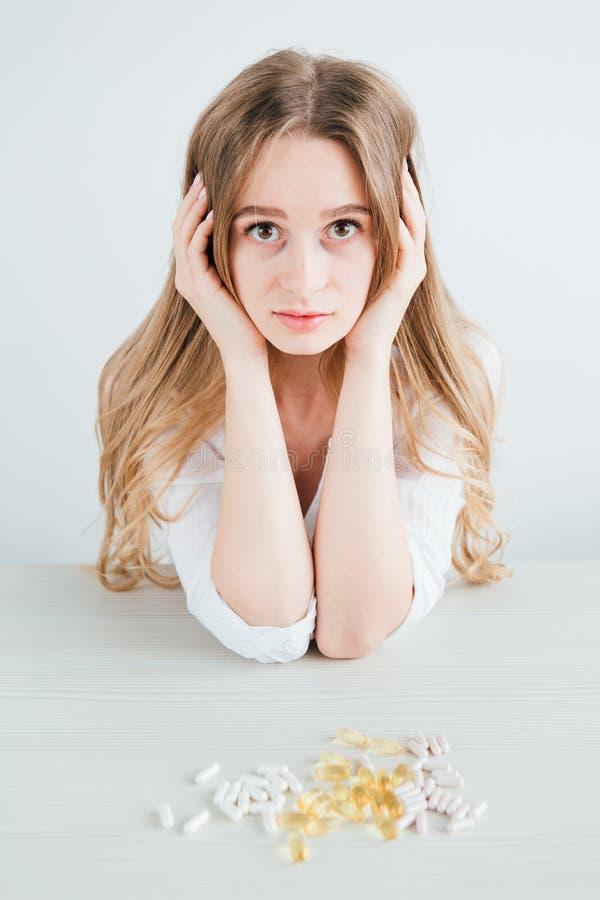 年轻美丽的病的女孩选择药片,片剂,维生素,膳食补充剂五颜六色的胶囊  免版税库存照片