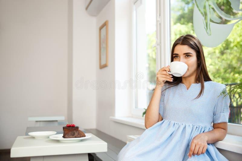 年轻美丽的白种人夫人喜欢喝和食用点心在现代咖啡店在中午 免版税图库摄影
