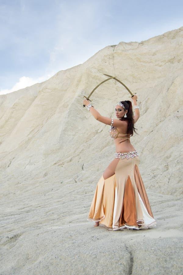 年轻美丽的白种人妇女肚皮舞表演者摆在有剑的沙漠的,后部 免版税库存照片