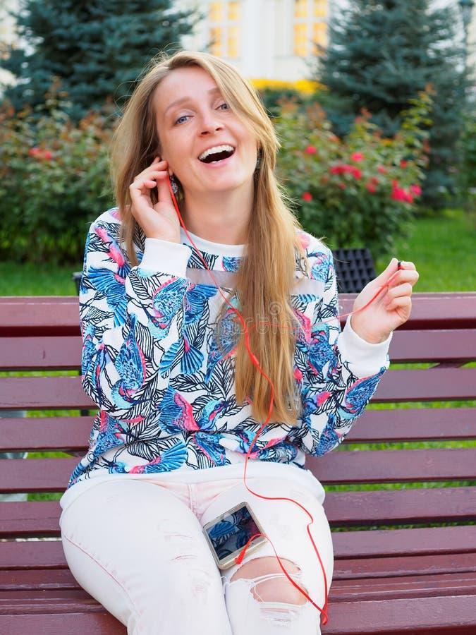 年轻美丽的白肤金发的女孩坐一条长凳在有微笑的智能手机的公园,说在电话里,听到音乐 免版税库存照片