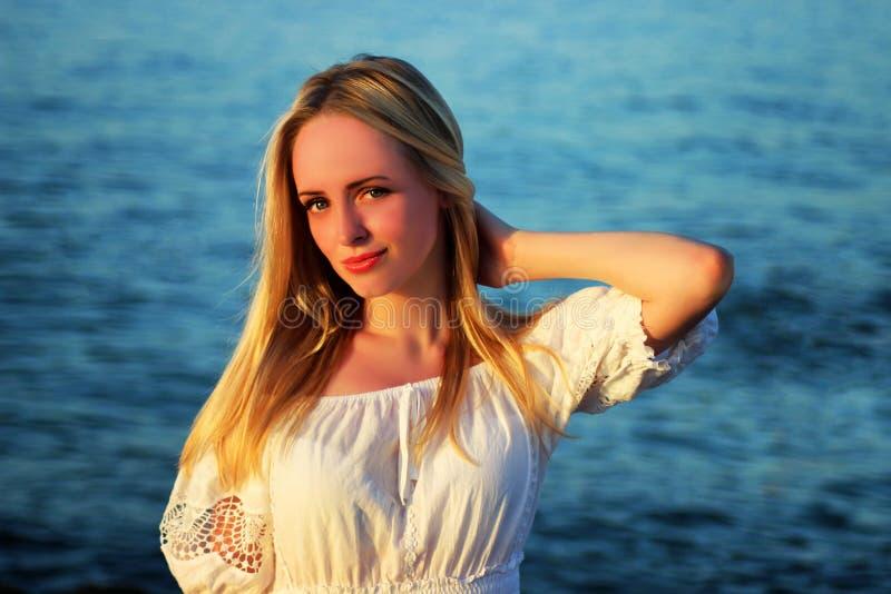 年轻美丽的白肤金发的女孩特写镜头画象在海背景的 库存照片