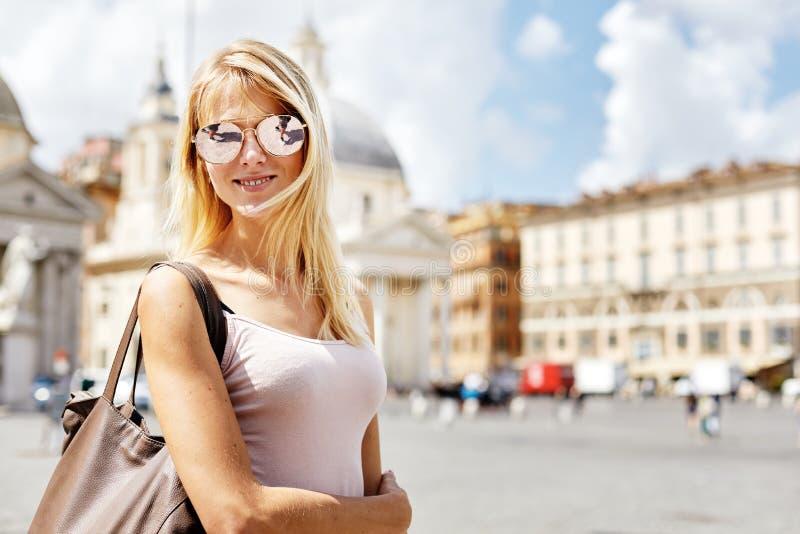 年轻美丽的白肤金发的女性在时髦的太阳镜和夏天给微笑的站立在老镇中心穿衣 免版税库存图片