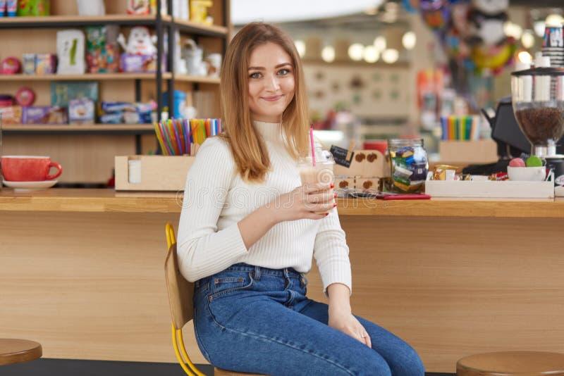 年轻美丽的白肤金发的妇女佩带的白色偶然衬衣和牛仔裤室内射击,坐在酒吧或咖啡馆,饮用的鸡尾酒, 免版税库存照片