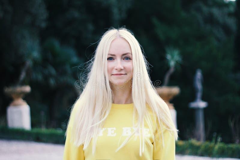 年轻美丽的白肤金发的妇女特写镜头画象有绿色公园植物的背景的 步行概念 新的成人 免版税图库摄影