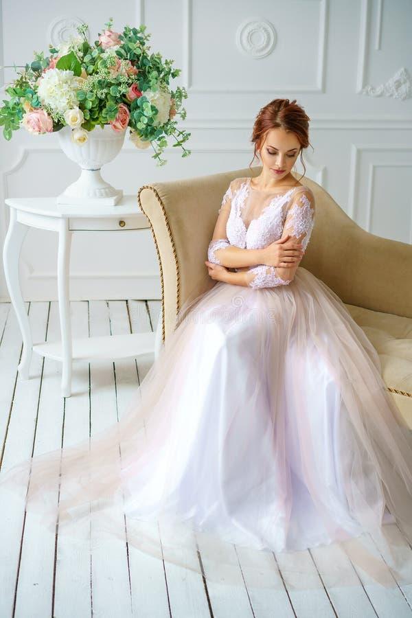 年轻美丽的红发妇女在一件美丽的精美礼服坐沙发,新娘 免版税库存照片