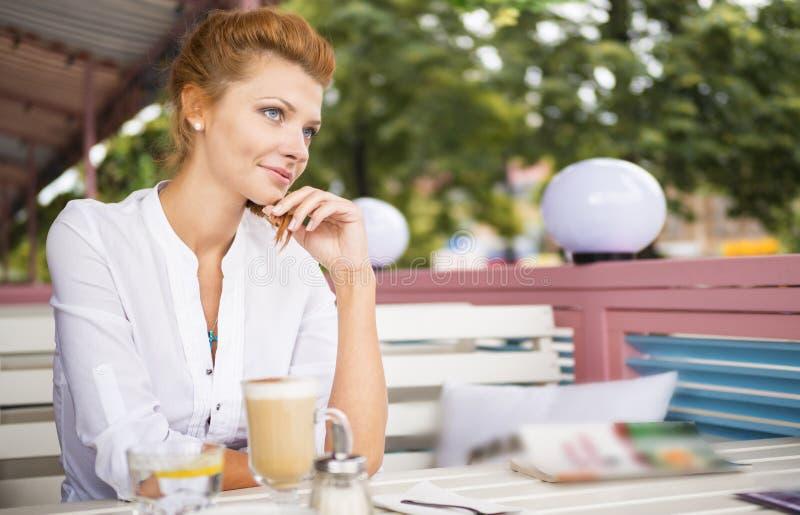 年轻美丽的红色头发妇女在夏天咖啡馆在街道坐,看并且喝从杯子的热的咖啡拿铁 图库摄影