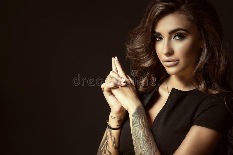 年轻美丽的被刺字的妇女画象有丰富的光亮的波浪发的和完善做停滞在射击姿态的手 免版税库存照片