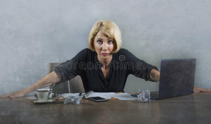 年轻美丽的被注重的和让烦恼的白肤金发的妇女与感觉的便携式计算机一起使用疲倦淹没由看起来的文书工作恼怒 免版税库存照片
