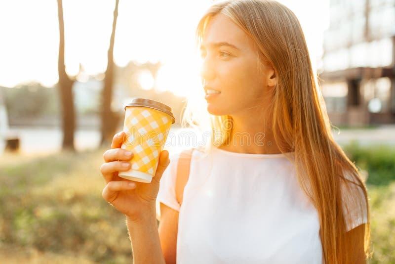 年轻美丽的走在城市附近的女孩饮用的咖啡,  库存照片