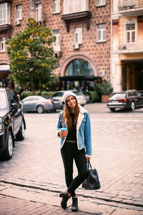年轻美丽的走在城市附近的浅黑肤色的男人饮用的咖啡 牛仔布夹克,摆在反对回合的窗口的都市背包 库存图片