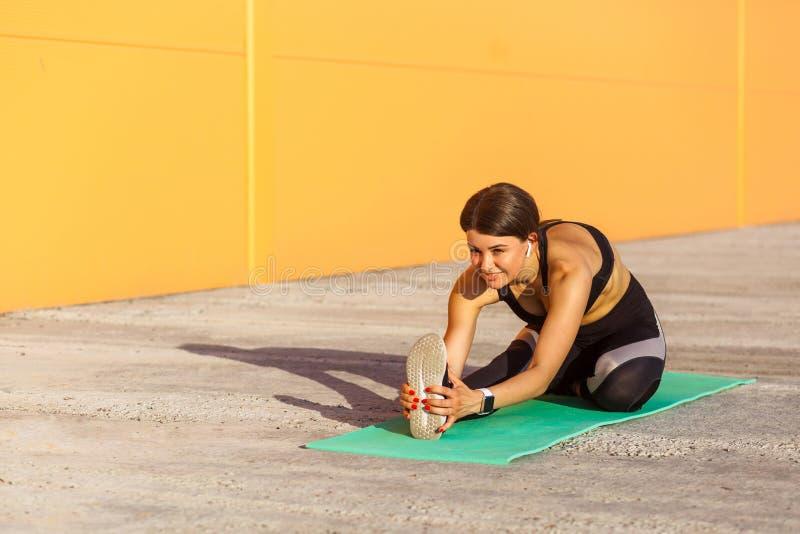 年轻美丽的运动的信奉瑜伽者女性在舒展在街道地板上的黑sportwear坐席子,看直接 图库摄影