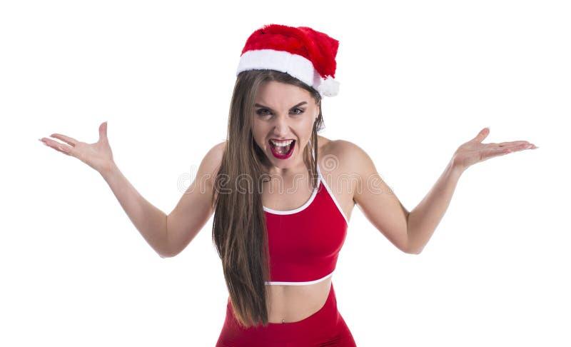 年轻美丽的运动的在被隔绝的白色背景疯狂和疯狂呼喊和叫喊的妇女佩带的圣诞节帽子 库存图片