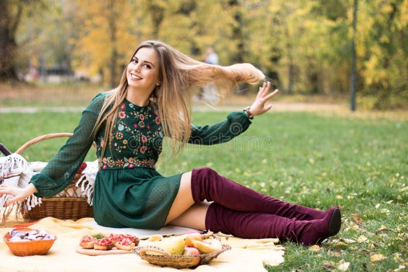 年轻美丽的金发女人在户外野餐 免版税库存照片