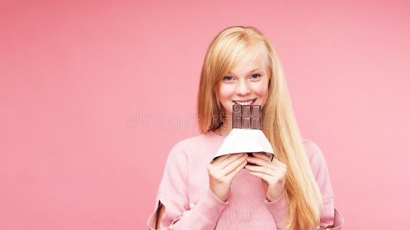 年轻美丽的金发碧眼的女人用巧克力 青少年的女孩咬住巧克力 诱惑吃禁止的巧克力 快乐的正面 库存照片
