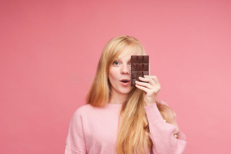 年轻美丽的金发碧眼的女人用巧克力 青少年的女孩咬住巧克力 诱惑吃禁止的巧克力 快乐的正面 免版税库存照片