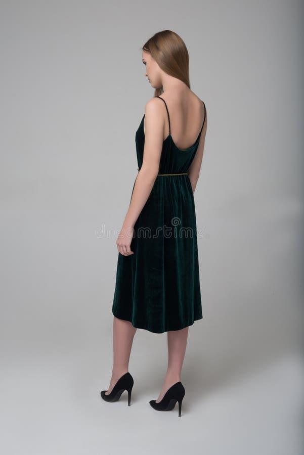 年轻美丽的长发女孩在深绿礼服走  免版税库存图片