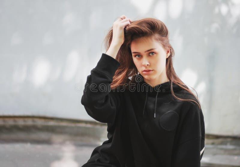 年轻美丽的长发女孩时装模特儿行家坦率的画象黑有冠乌鸦的在墙壁背景 免版税库存图片