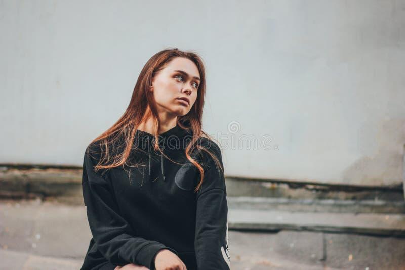 年轻美丽的黑有冠乌鸦的长发不快乐的女孩时装模特儿行家坦率的画象在肮脏的墙壁上 图库摄影