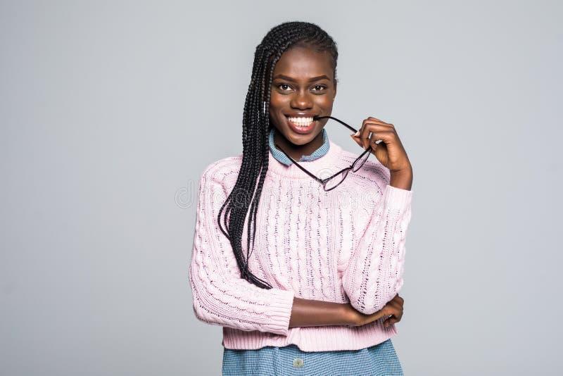 年轻美国黑人的在灰色隔绝的妇女偶然每日生活方式学生咬住的玻璃 免版税库存照片
