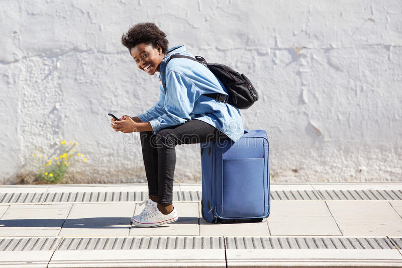 年轻美国黑人的妇女坐手提箱在有手机的铁路平台 免版税库存照片