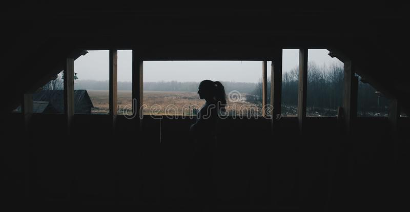年轻美女剪影在村庄 在一个森林妇女女孩的背景的模型在窗口前面的 免版税库存照片