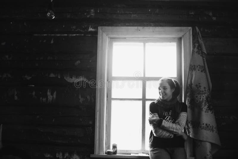 年轻美女剪影在村庄 在一个森林妇女女孩的背景的模型在窗口前面的 图库摄影