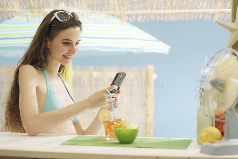 年轻美女喝一杯在海滩 图库摄影