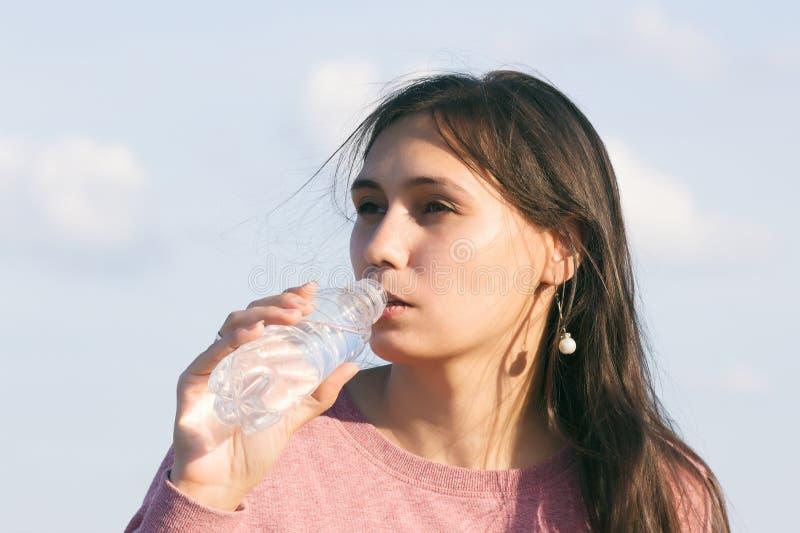 年轻美女喝水 免版税库存照片