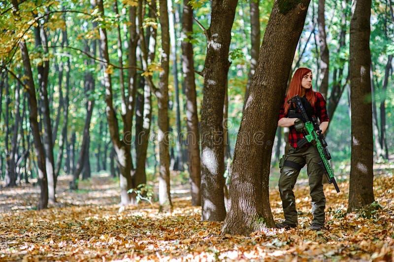 年轻美女在有步枪的森林里 免版税库存照片