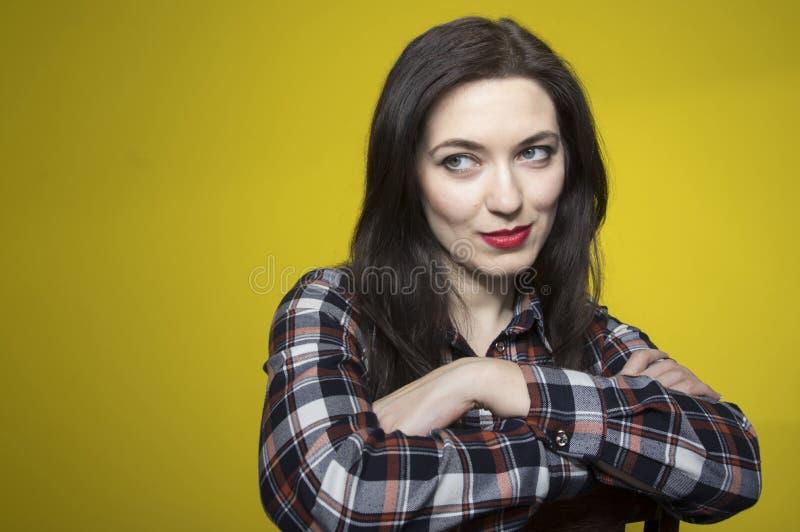 年轻美女坐在格子衬衫的一把椅子,看对与胳膊的边横渡了 库存图片
