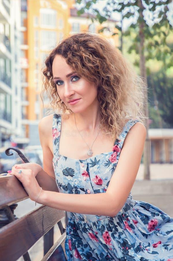 年轻美女坐长凳在商业中心附近 她微笑,看起来被送到照相机 佩带一蓝色花卉 免版税库存照片