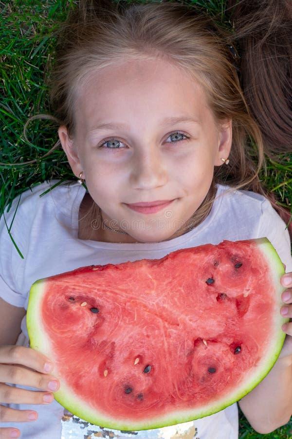 年轻美女夏天画象 室外微笑的childr 青少年用西瓜 吃西瓜的愉快的微笑的女孩在公园 免版税图库摄影