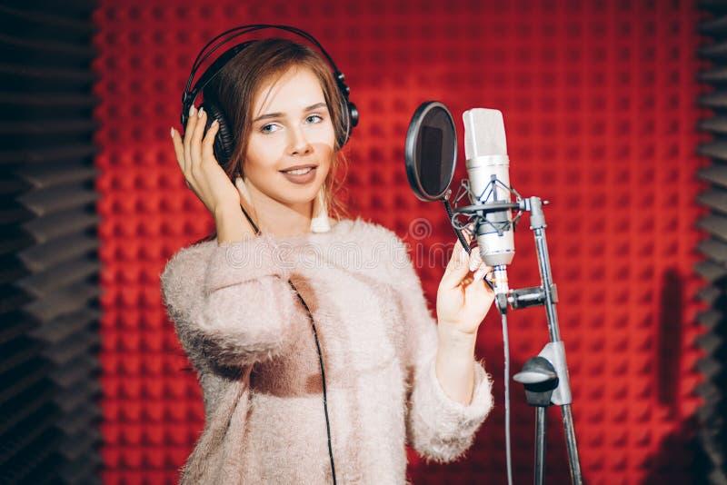 年轻美女录音一首歌曲在有红色墙壁的一个专业演播室 免版税库存图片