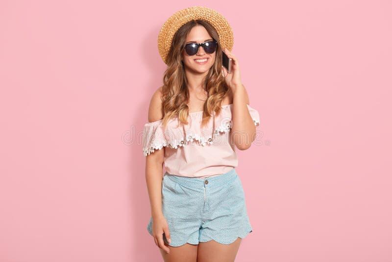 年轻美女接近的画象说在电话里 时髦女孩佩带的夏天衣裳和草帽 滑稽和正面 库存照片