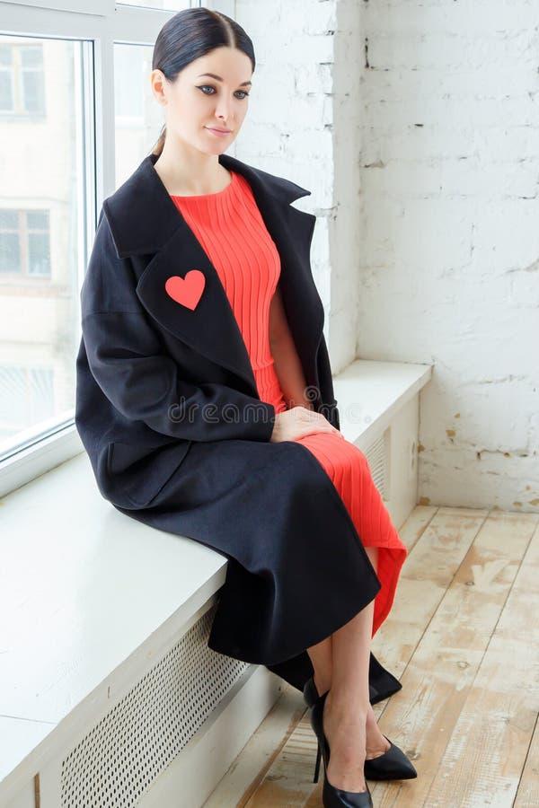 年轻美女时尚画象红色礼服和外套的 库存照片