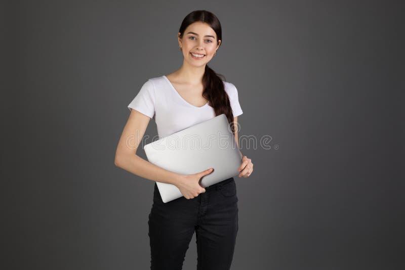 年轻美女有愉快的表情,拿着膝上型计算机,微笑 免版税图库摄影