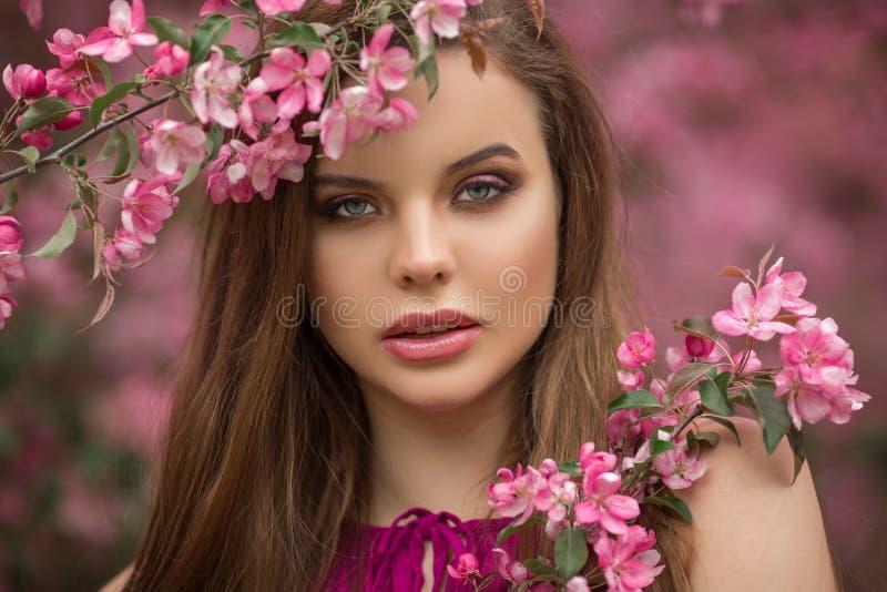 年轻美女特写镜头浪漫画象在开花有桃红色花的苹果庭院里 免版税库存图片