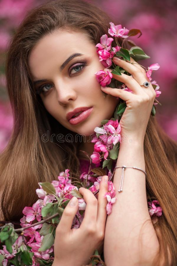 年轻美女特写镜头浪漫画象在开花的桃红色苹果庭院里 免版税图库摄影
