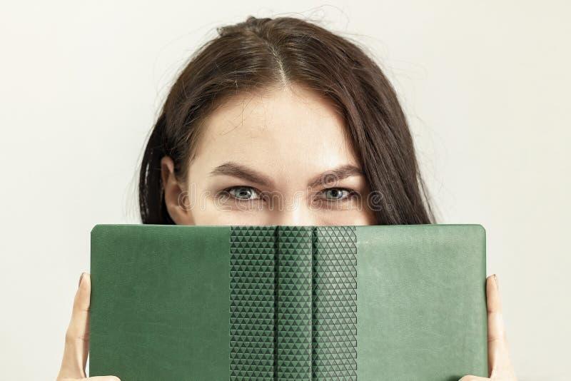 年轻美女用书,日志,笔记本盖了她的面孔 免版税库存图片