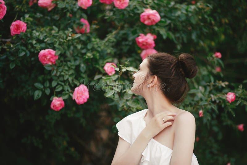 年轻美女画象关闭与摆在与桃红色玫瑰花的完善的皮肤在庭院里 库存照片