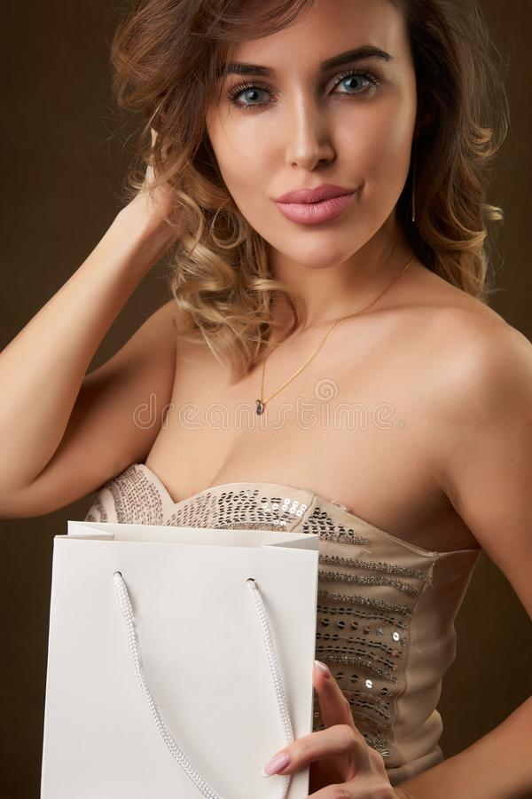 年轻美女画象有购物带来的反对黑暗的背景 免版税图库摄影